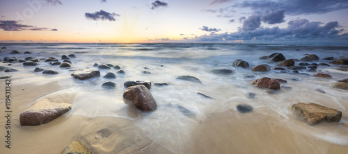 Fototapeta Zachód słońca nad bałtycką plażą,głazy piastowskie na wyspie Wolin  obraz