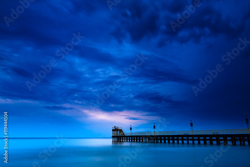 Fotobehang Donkerblauw Sandy coast with dramatic sky and pier during sunset.