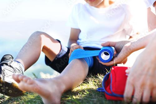 Bandażowanie nogi. Matka opatruje dziecięce kolano bandażem elastycznym.
