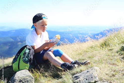 Fototapeta Wakacje w górach.  Dziecko je kanapkę na górskim szlaku  obraz