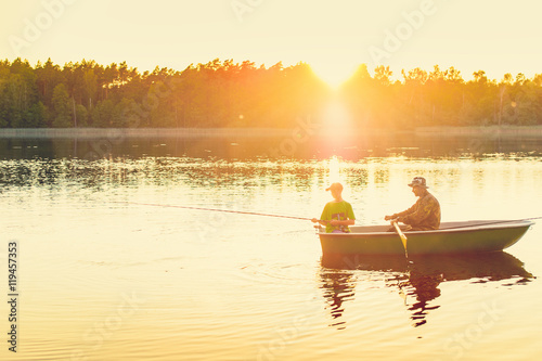 Poster Peche father and son catch fish from a boat at sunset