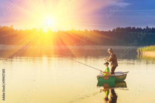 Plakat ojciec i syn łowią ryby z łodzi o zachodzie słońca