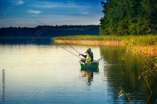 Fotografia  father and son catch fish from a boat at sunset
