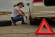 woman makes replacement tires in the car for a sign of attention