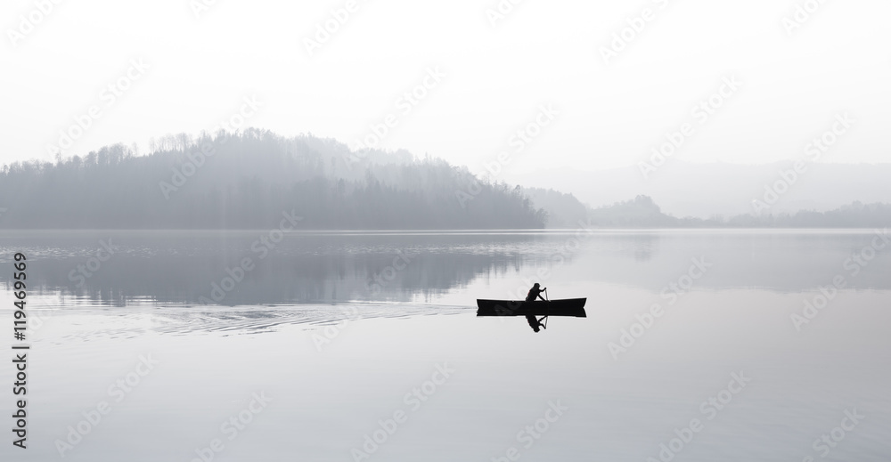 Fototapeta Autumn. Fog over the lake. Silhouette of mountains in the background. The man floats in a boat with a paddle.