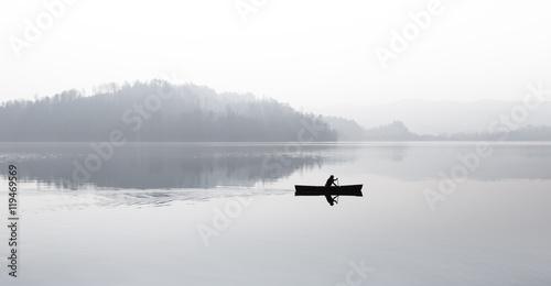 Zdjęcie XXL Jesień. Mgła nad jeziorem. Sylwetka gór w tle. Mężczyzna pływa w łodzi z wiosłem.