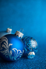 Blue Xmas Ornaments On Dark Blue Glitter Background With Space For Text. Merry Christmas Card. Winter Holiday Theme. Happy New Year.
