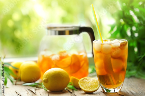 Poster Sap Glass of iced tea on wooden table and blurred green background