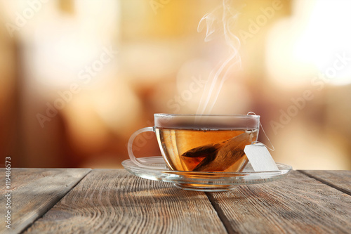 Fotobehang Thee Glass cup of tea on wooden table and blurred color background