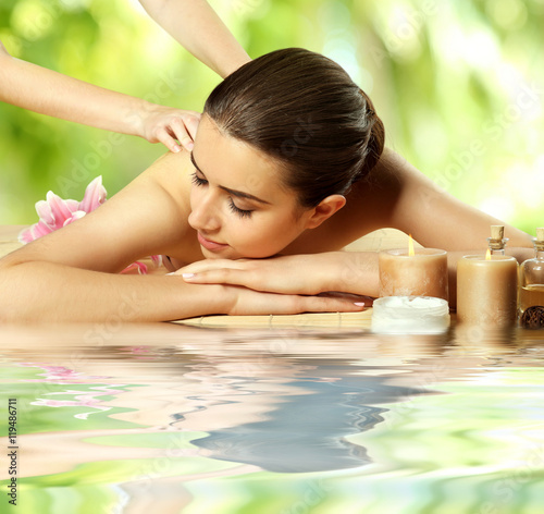Fototapety, obrazy: Spa concept. Beautiful woman having massage on table near water. Blurred green foliage background.