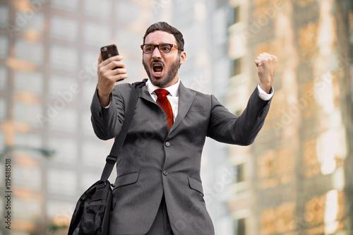 Stock market investor celebrating big win financial good news success achievement cell phone