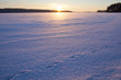 A wintry sunset. An image of a sunset on a cold winter day. Sun is going down behind a lake covered with ice and snow and footprints of an animal. Some forest is in the background.