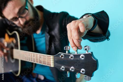 Valokuvatapetti Bearded hipster man hand adjusting on acoustic guitar.