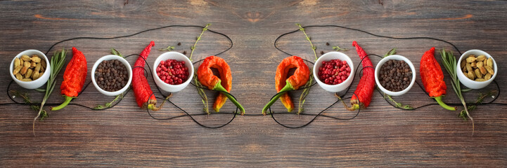 FototapetaConcept of hot spice cuisine and seasoning - peppers, herbs, condiment. Black pepper, pink pepper, cardamon seeds, thyme, rosemary and chili peppers on wooden table. Wide panorama, horizontal