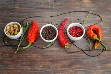 Concept of hot spice cuisine and seasoning - peppers, herbs, condiment. Black pepper, pink pepper, cardamon seeds, thyme, rosemary and chili peppers on wooden table.
