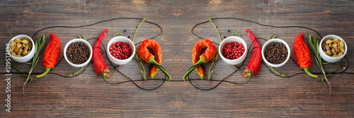Concept of hot spice cuisine and seasoning - peppers, herbs, condiment. Black pepper, pink pepper, cardamon seeds, thyme, rosemary and chili peppers on wooden table. Wide panorama, horizontal