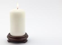 Single White Lit Candle On Whi...