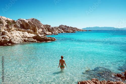 Photo  Frau steht in glasklarem Wasser einer Bucht