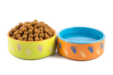 Dry Dog Food And Water In Ceramic Colorful Bowls Isolated On White.