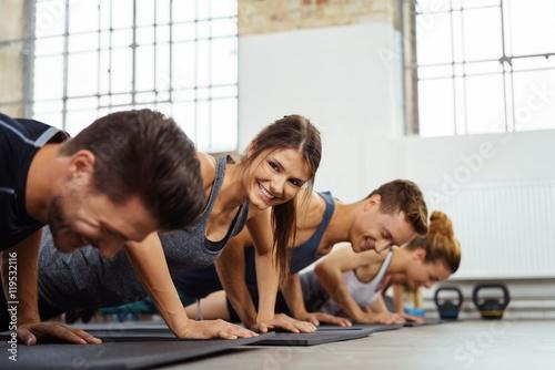 lachende frau trainiert in einer gruppe im fitness-studio