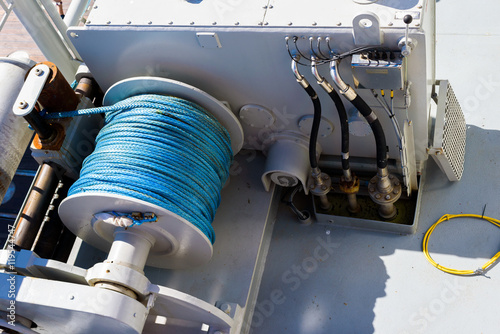 Foto Large spool with blue plastic rope on a tugging winch on a ship.