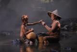 Stara kobieta i chłopiec cieszyli się z połowów, uśmiechu i szczęścia w wodospadzie w Tajlandii - 119547555