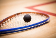 Close Up Of A Squash Ball On Racket Over Wooden Background