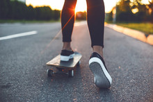 Young Skateboarder Legs Riding On Skateboard In Front Of The Sun