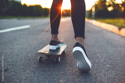 Vászonkép young skateboarder legs riding on skateboard in front of the sun