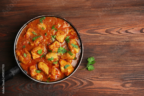 Photo  Tasty chicken curry in pan on wooden background
