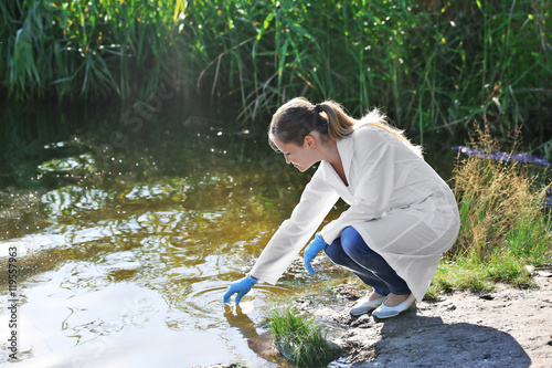 Valokuva  Woman with flask for expertise. Environmental pollution concept