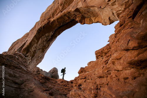 Low angle view of person standing at rock formation against clear sky