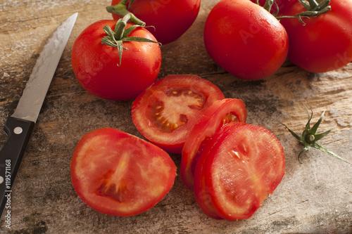 Fotografie, Obraz Sliced succulent red tomatoes beside serrated knife