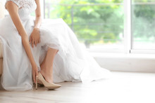 Bride In A Beautiful Wedding Dress Putting On Shoes