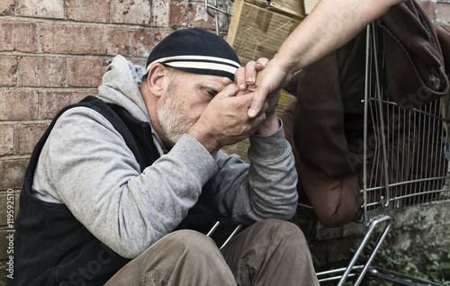 Homeless man taking an unrecognisable woman's hand Canvas Print