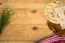 Checkered Napkin, Pita Bread And Cute White Wildflowers On Wooden Background. Place For Text. Top View.