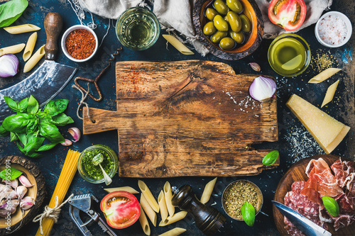 Nourriture Italian food cooking ingredients on dark background with rustic wooden chopping board in center, top view, copy space