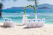 site aménagé avec des fleurs blanches pour célébration d'un mariage sur plage des Seychelles