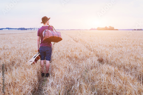 young son leaving home, romantic travel background, man with guitar and road bag Canvas