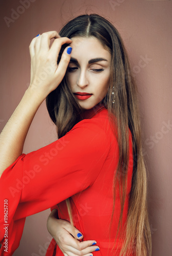 Fényképezés  Elegant beautiful young girl with red long dress, long blonde hair, red lipstick