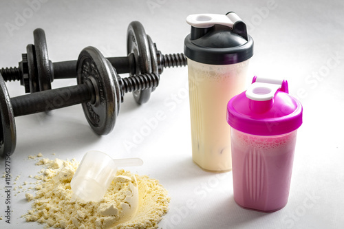 Fotografia  Fitness and workout concept with dumbbells, protein shakers  and a scoop in protein powder