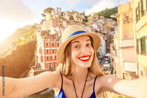 Poster Ligurie Young female traveler making selfie photo on the old coastal town in Riomaggiore in Italy. Happy vacations in Italy