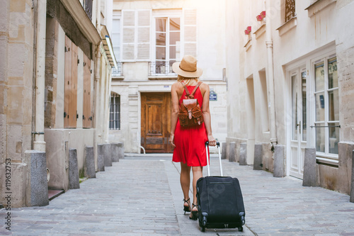 Fotografía travel background, woman tourist walking with suitcase on the street in european