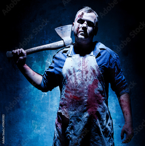 Photo  Bloody Halloween theme: crazy killer as butcher with an ax