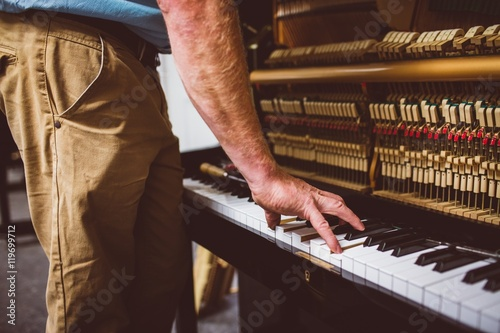 Midsection of technician playing piano in workshop