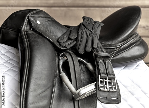 Acrylic Prints Horseback riding Dressage Saddle with Stirrup, Riding Gloves and Girth