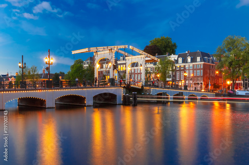 Photo  Magere Brug, Skinny bridge, with night lighting over the river Amstel in the cit