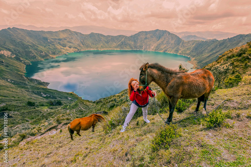 Fotomural  Young Woman Hiking With Two Horses