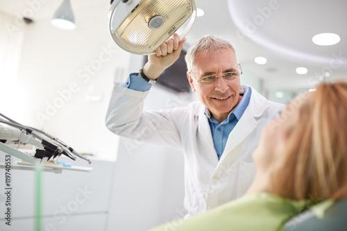 Fotografie, Obraz  Dentist adjust searchlight before starting work.