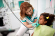 Dentist on working place in dental practice with patient